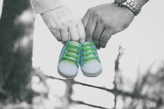 Parent holding a pair of kids shoe. Surrogacy in Georgia for parenthood.