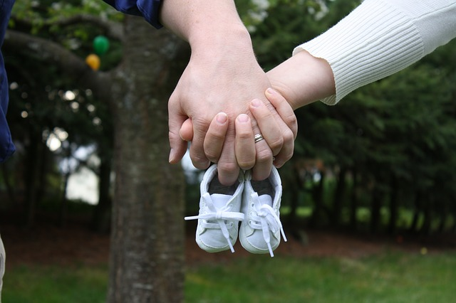 Couple holding baby shoes (expecting a baby). Pic for Myth Baby boy or girl